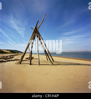 Log teepee on sandy beach - Stock Photo
