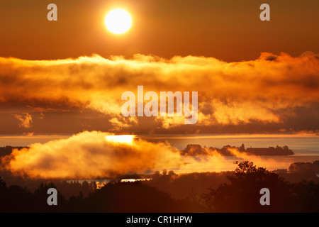 Sunrise, lake Chiemsee and Frauenchiemsee island, also known as Fraueninsel island, view from Ratzinger Hoehe, Chiemgau - Stock Photo