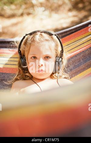 Girl listening to headphones outdoors - Stock Photo