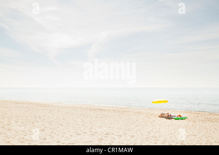 Umbrella and towels on beach - Stock Photo