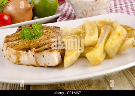 grilled loin steak with french fries on a plate - Stock Photo