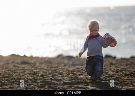 Toddler carrying sunhat on beach - Stock Photo