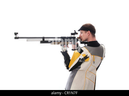 Man standing sideways taking aim with an air rifle isolated on white - Stock Photo