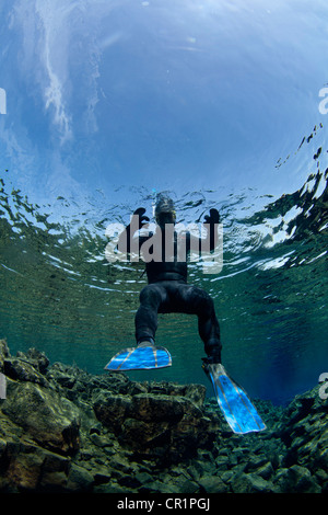 Diver swimming by rock formations - Stock Photo
