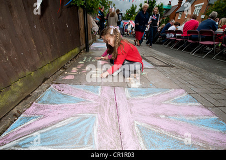 Cakes, bunting, face paint and champagne are enjoyed at a street party in South West London despite the odd burst - Stock Photo