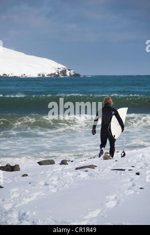 Surfer carrying surfboard on snowy beach - Stock Photo