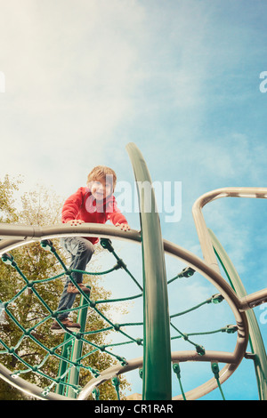 Boy climbing on jungle gym at park - Stock Photo