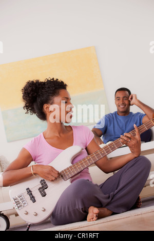 USA, California, Los Angeles, Woman playing electric guitar, man in background - Stock Photo