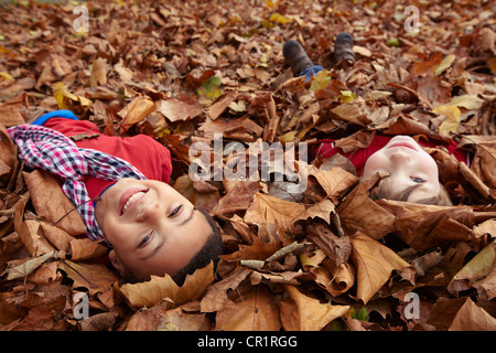 Children playing in autumn leaves - Stock Photo