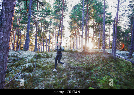Woman running in forest - Stock Photo