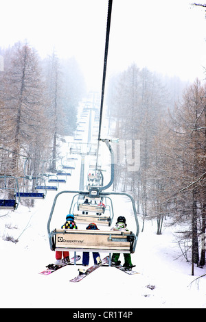 Snowboarders on ski chair lift during blizzard snow storm in Bardonecchia Italy - Stock Photo