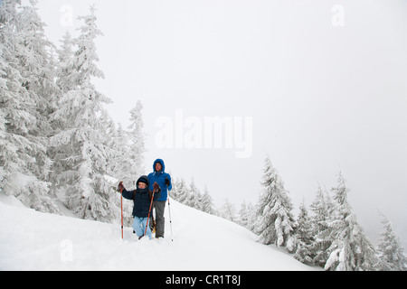 Father and son snowshoeing on hillside - Stock Photo