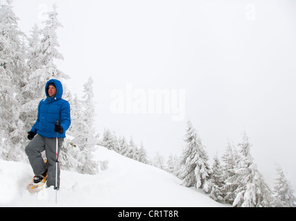 Man snowshoeing on snowy hillside - Stock Photo
