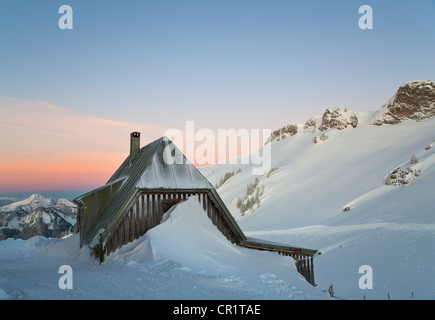 Snow piled up by house on hillside - Stock Photo
