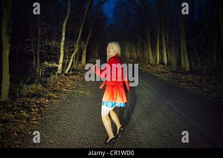 Woman running in fear in woods at night - Stock Photo