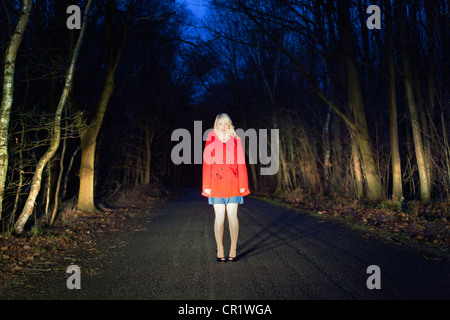 Woman standing on road in woods - Stock Photo