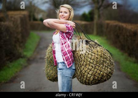 Teenage girl carrying hay on dirt path - Stock Photo