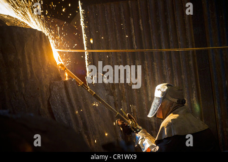 Welder at work in steel forge - Stock Photo