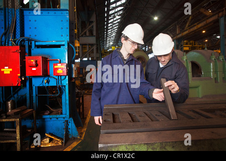 Workers examining metal in steel forge - Stock Photo