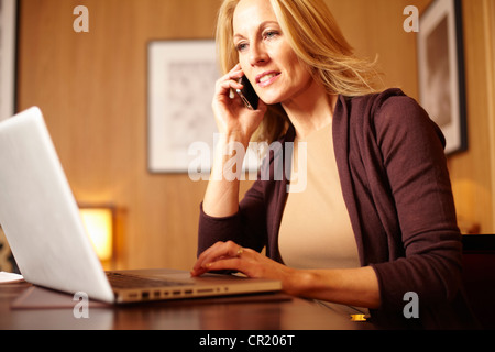 Businesswoman using laptop in hotel room - Stock Photo
