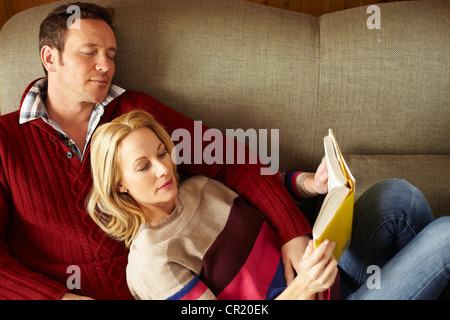 Couple relaxing on sofa together - Stock Photo