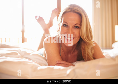 Smiling woman laying on bed - Stock Photo