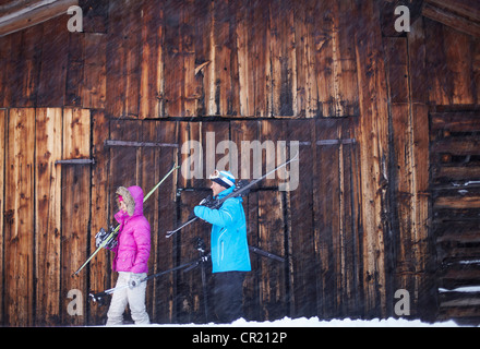 Couple carrying skis and poles in snow - Stock Photo