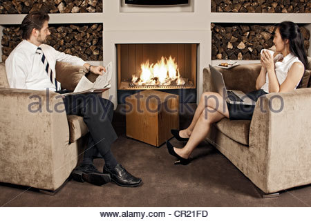 Business people sitting by fire - Stock Photo