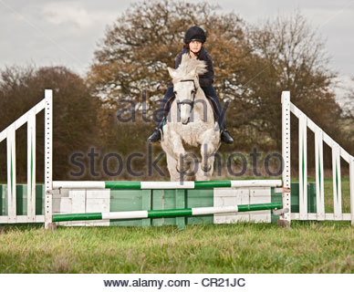 Girl racing horse over jump on course - Stock Photo
