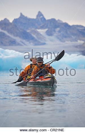 Men rowing canoe on still glacial sea - Stock Photo