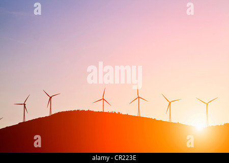 Silhouette of windmills on rural hills - Stock Photo