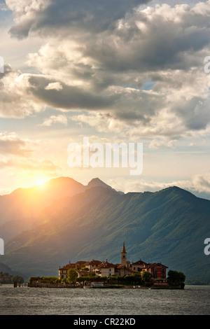Sun shining over castle built on island - Stock Photo