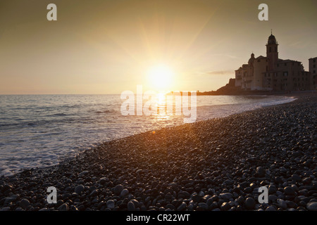 Sun setting over rocky beach - Stock Photo