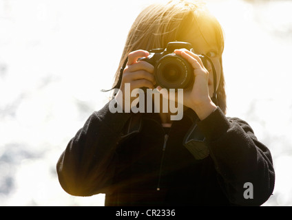 Girl taking pictures outdoors - Stock Photo