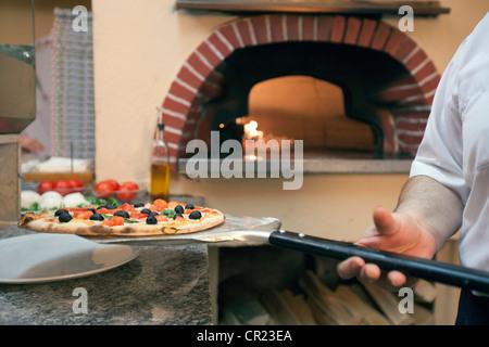 Chef holding pizza on spatula - Stock Photo