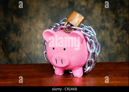 A pink piggybank chained up and locked. Image can be used for financial protection inferences or other investment messages.
