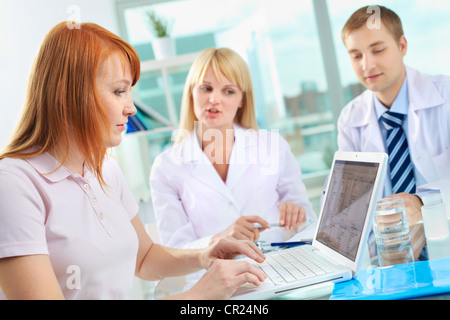 Portrait of female patient looking at results of medical test in laptop - Stock Photo