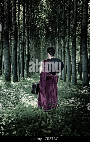 a woman is walking through a forest with a hat and a suitcase in a period dress
