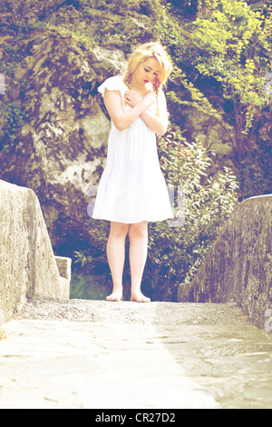 young woman in a white dress stands barefoot on a bridge - Stock Photo