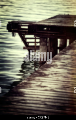 old wooden pier with stairs to the lake - Stock Photo