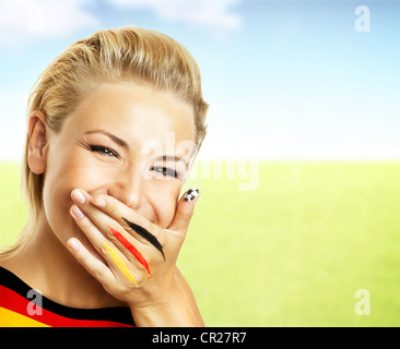 Smiling football fan, closeup on face, female covering mouth with painted in flag colors hand, woman expressing - Stock Photo