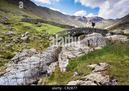 A hiker crosses Stockley Bridge on a bright spring day from Seathwaite Fell in the Lake District, Cumbria UK. - Stock Photo