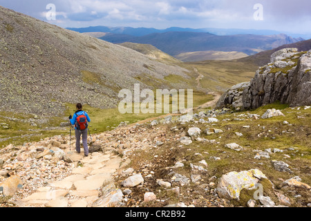 A hiker descends the steep path from the summits of Ill & Broad Crag in the Lake District. The Langdale Pikes can be seen in the