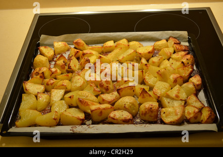 Freshly baked potatoes on baking paper in oven tray. Healthy cheap food from vegetables. - Stock Photo