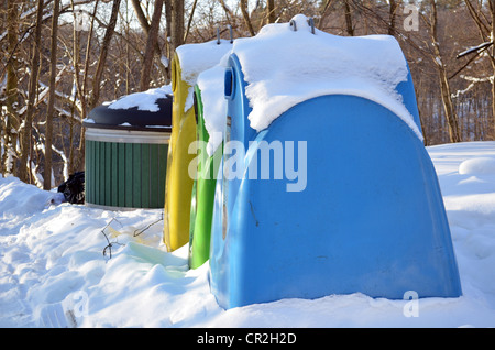 Waste sorting containers covered with snow during winter. Paper, glass and plastic. Blue, green and yellow color - Stock Photo
