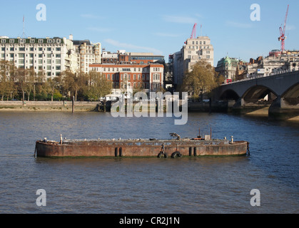 A steel barge is anchored in the River Thames by Waterloo bridge. The Savoy Hotel is to the left. South Bank, London - Stock Photo