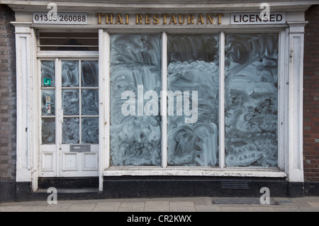 A closed down Thai restaurant, one of many conspicuous high street casualties of the global economic crisis in 2012. - Stock Photo