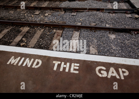 Edge of railway station platform with painted warning sign - Stock Photo