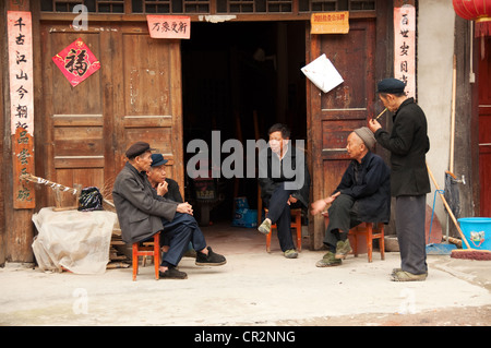 Elderly Dong men seated in front of a door, Zhaoxing Dong Village, China - Stock Photo
