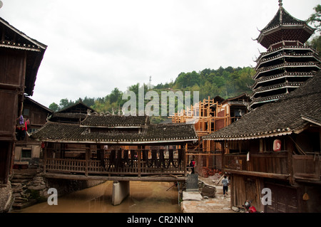 A small 'Wind and Rain' bridge on a water stream and an ancient Drum Tower, Zhaoxing Dong Village, China - Stock Photo